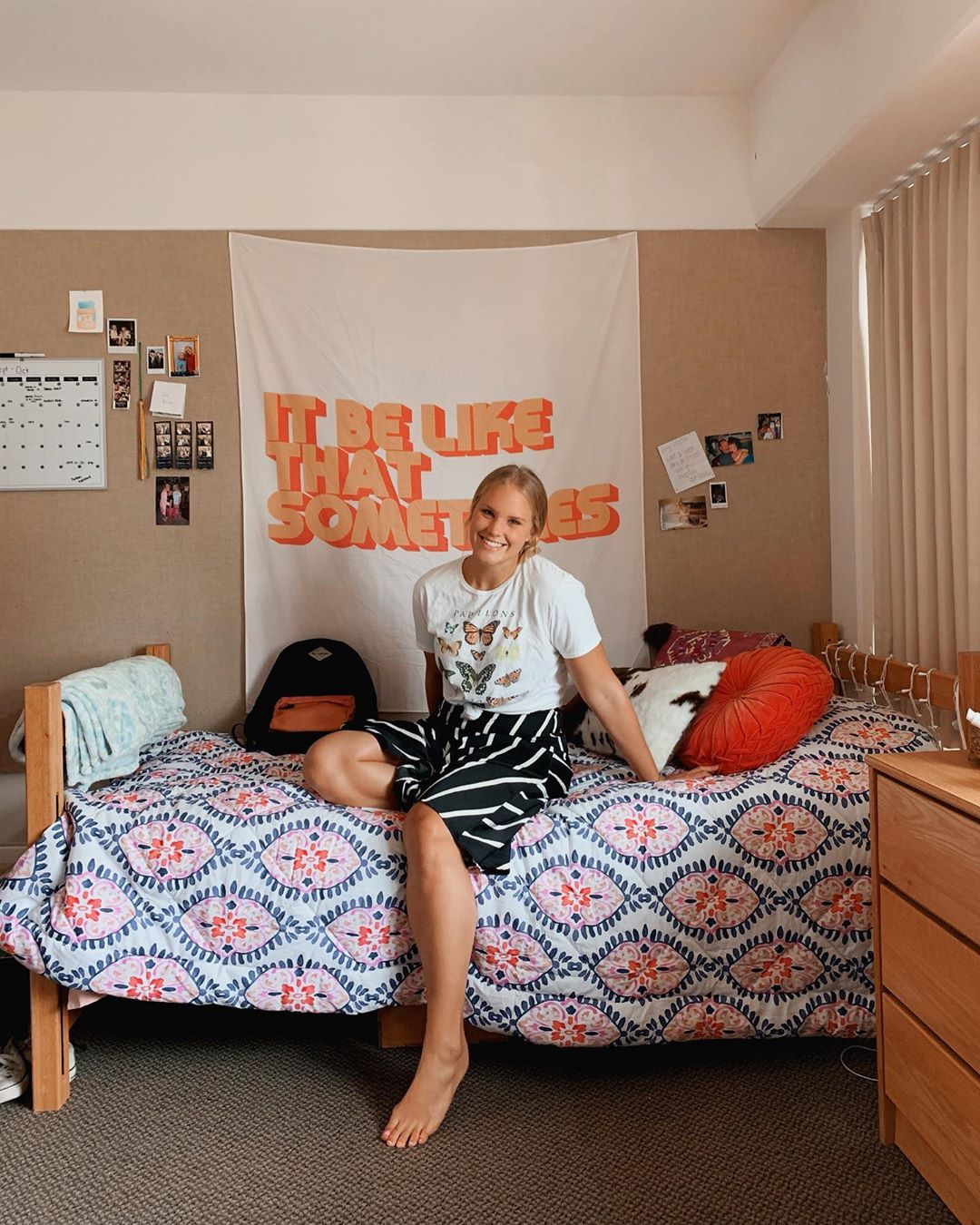 dorm room at UCLA with blue and orange bedspread. Orange words tapestry behind smiling female student posing on bed