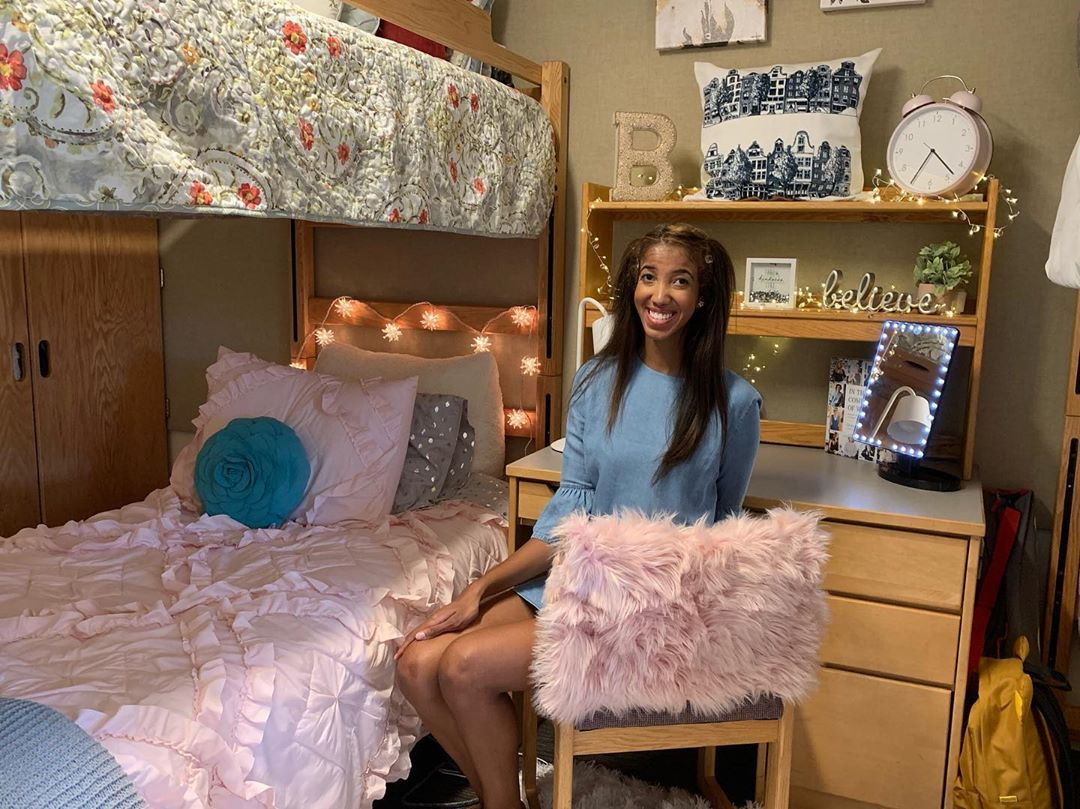 happy college girl posing in her pink decorated dorm room in UCLA