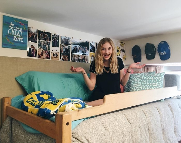 female college student in her blue accent decorated dorm at UCLA with a big smile
