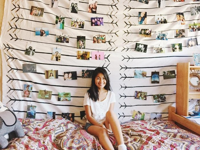 happy college girl sitting on her dorm room bed with tapestry and pictures behind her