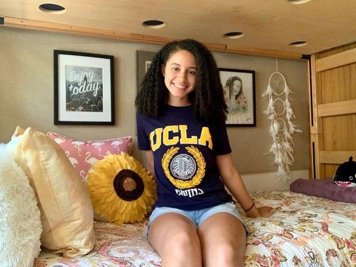 college girl wearing UCLA tshirt sitting on her dorm room bed