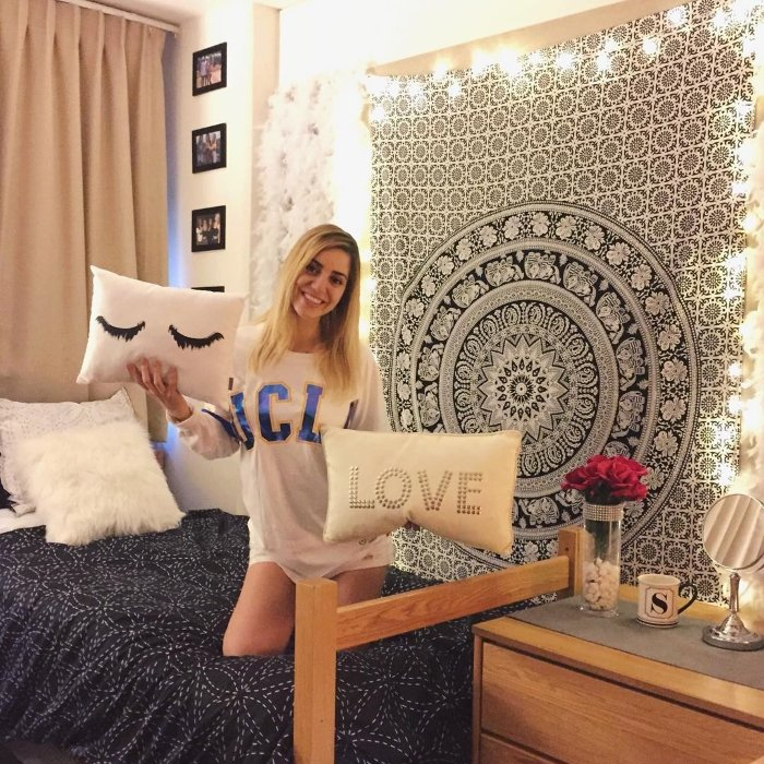 college girl at UCLA smiling, holding pillows and posing in her dorm