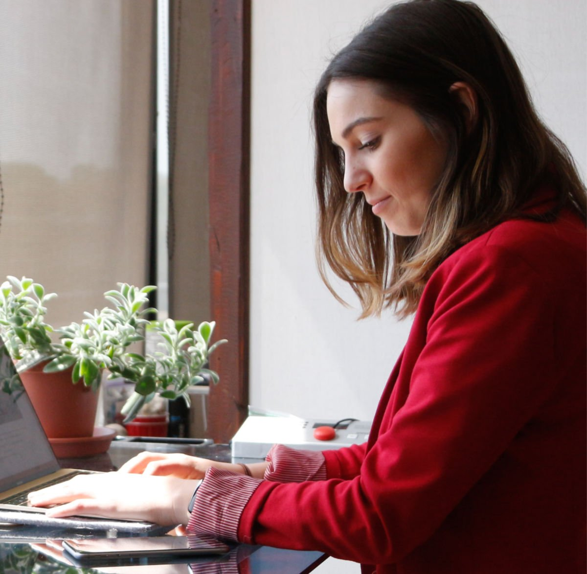 millennial woman smiling while working on laptop