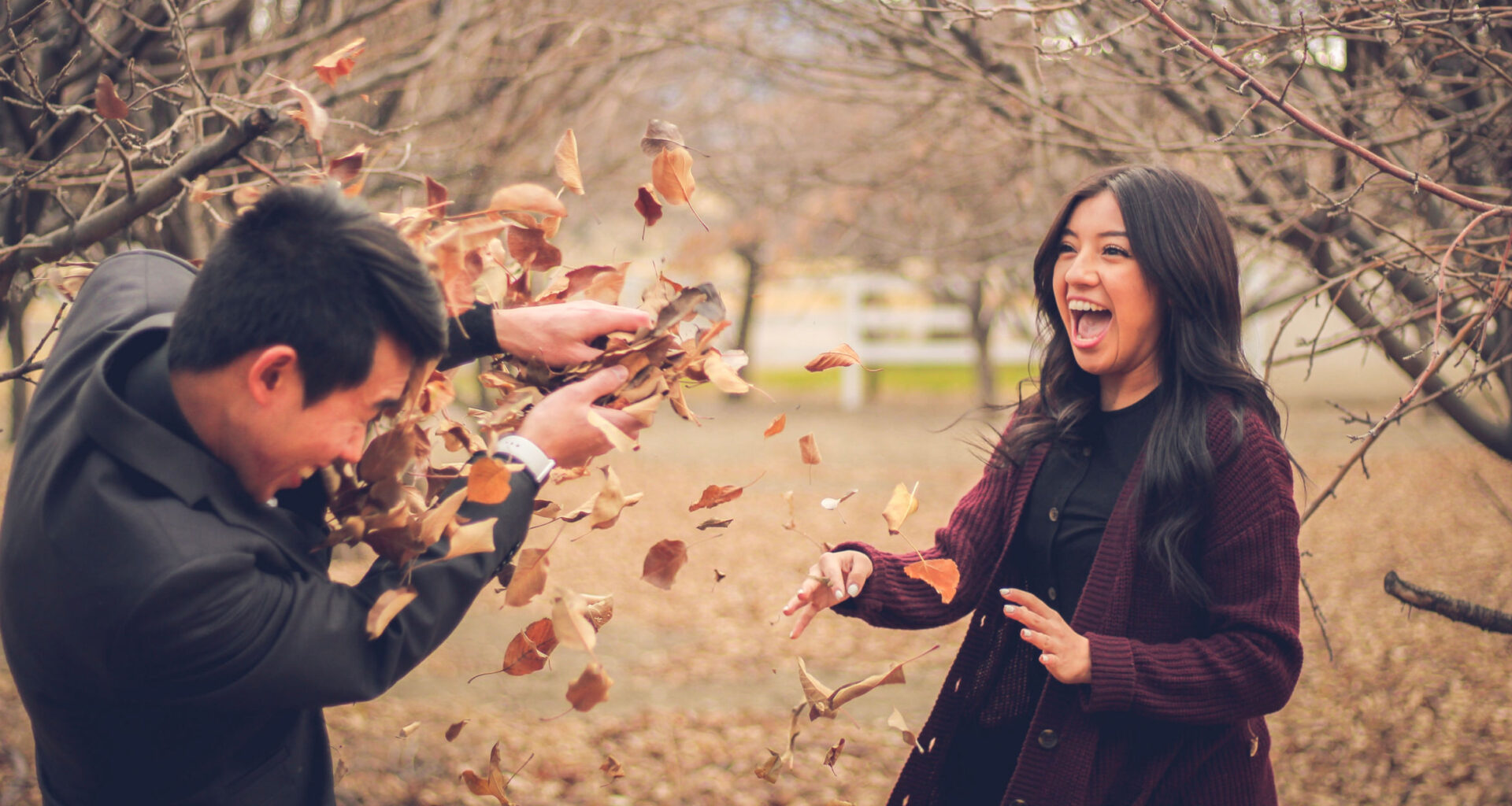 male and female high school teens tossing fall leaves at each other