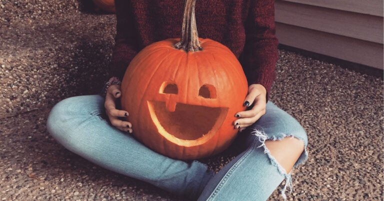teenage girl holding carved pumpkin with smile