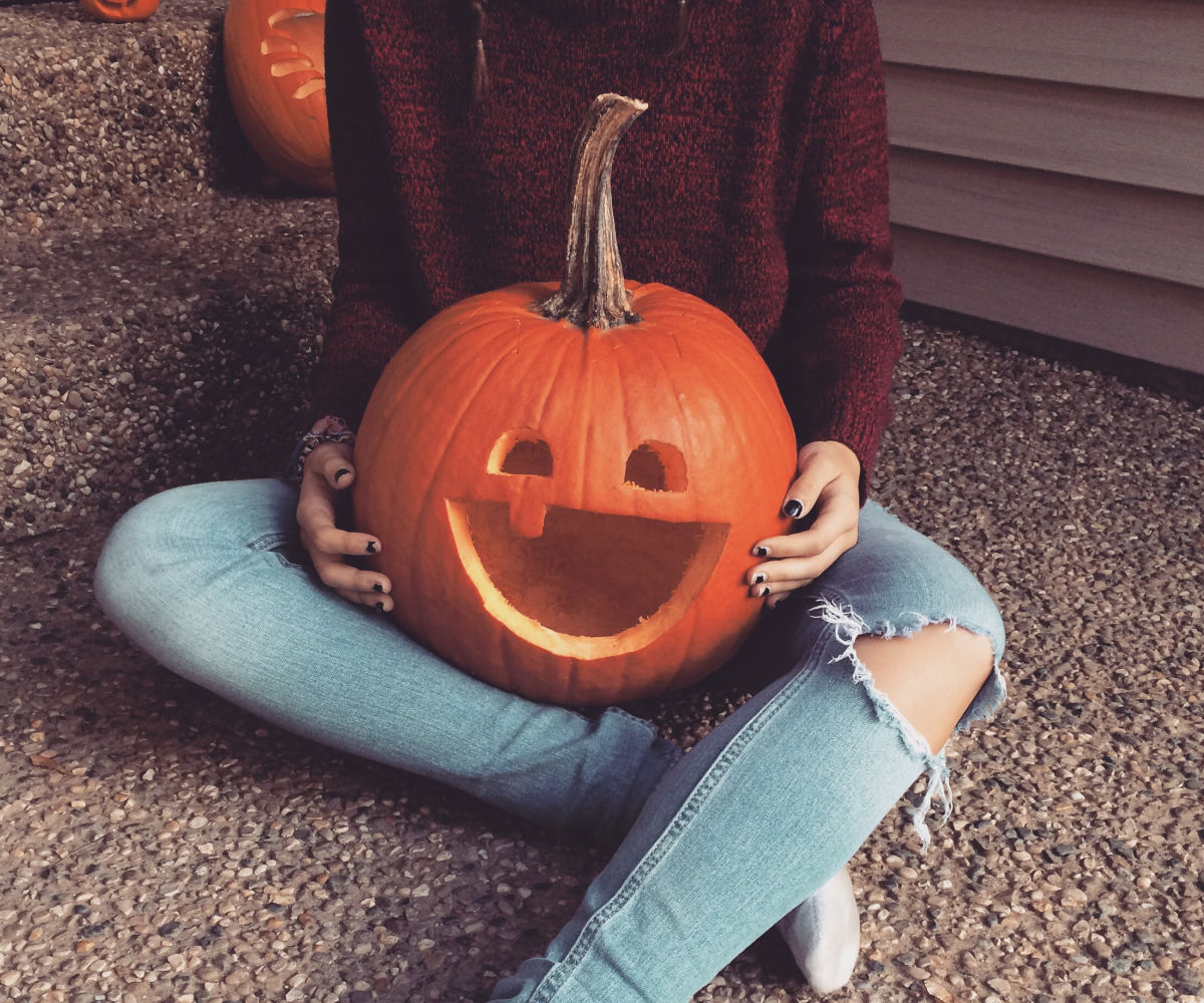 high school girl with carved smiling pumpkin in her lap