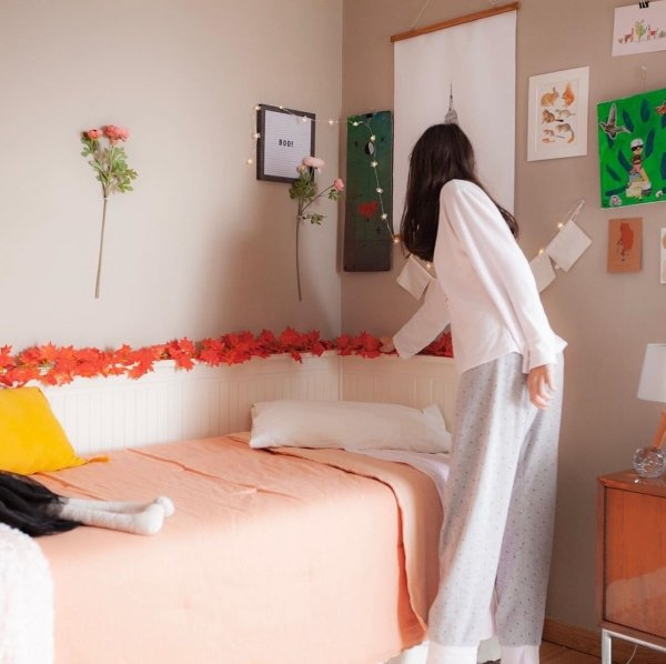 college girl adjusting her dorm room fall/Halloween decoration by her bed