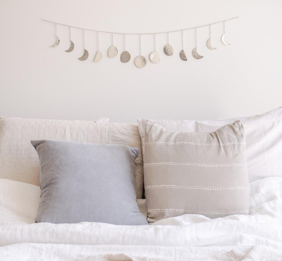silver moon phase garland decoration hanging on wall above bed