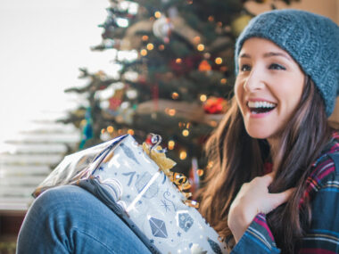 laughing young woman holding a gift with a Christmas tr