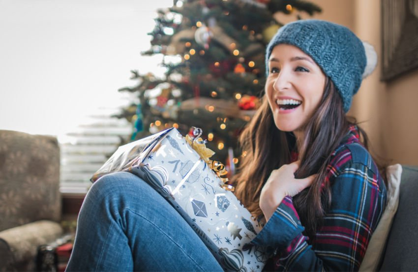 college girl laughing while holding a wrapped gift