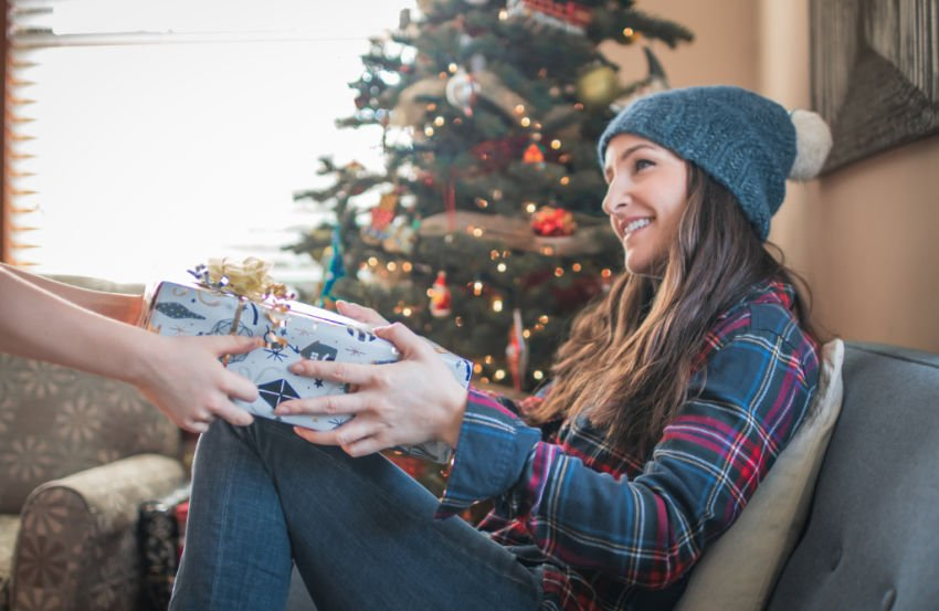 smiling young woman being handed a wrapped Christmas gift