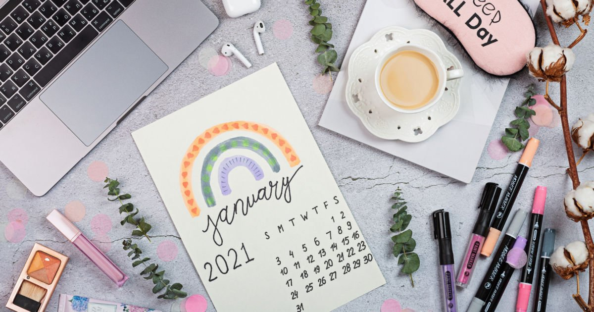 cute january calendar ready for planning next to various items like a laptop