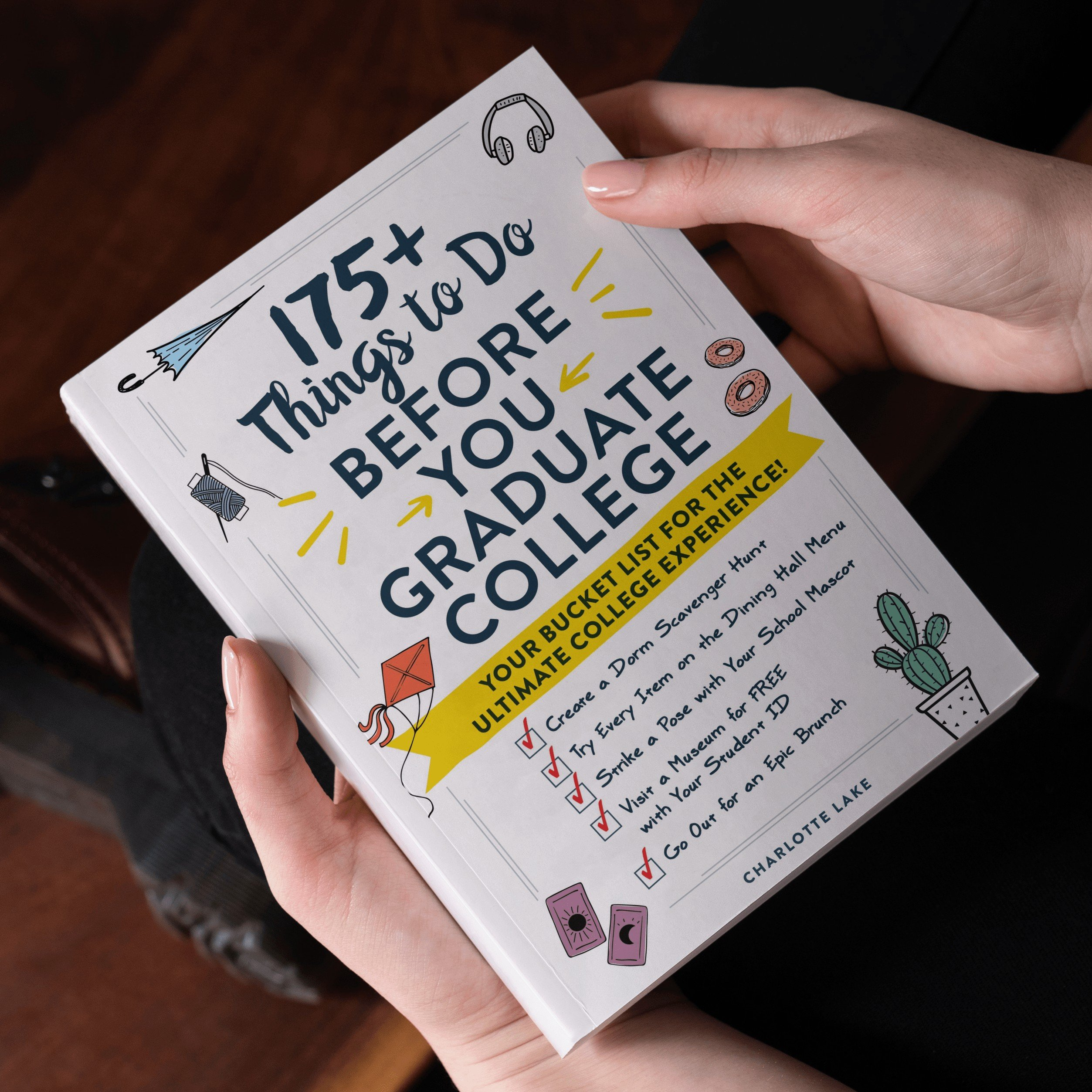 175+ Things to Do Before You Graduate College book held in hands in front of dark background
