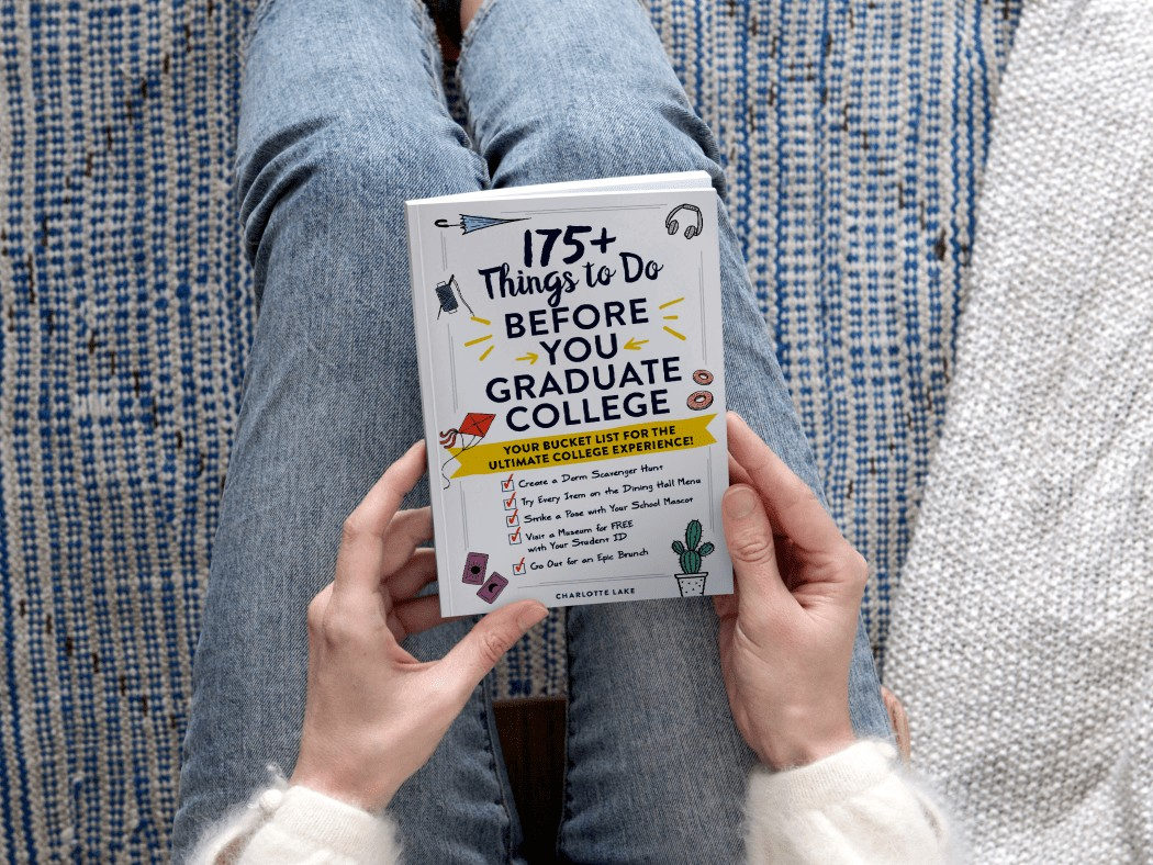 white cover book with colorful graphics held in hands above lap