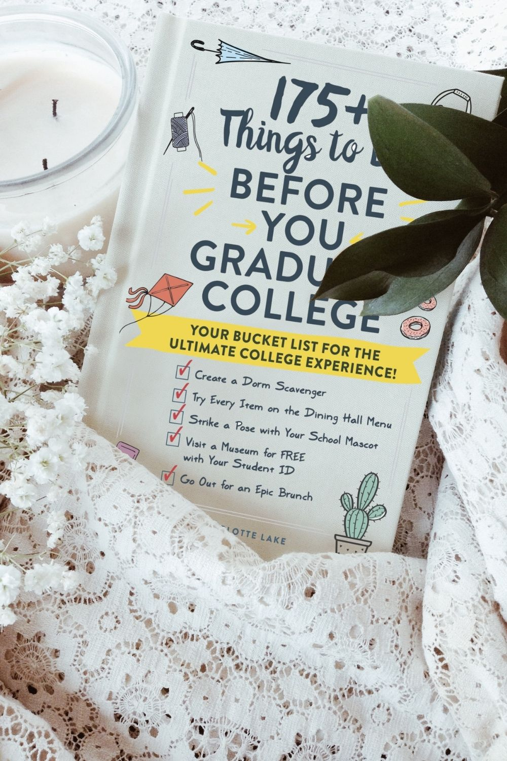 white college bucket list ideas book next to lacey fabric, a candle, and a plant