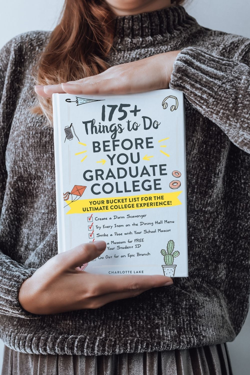 woman in grey clothing with red hair holding book of things to do before you graduate college