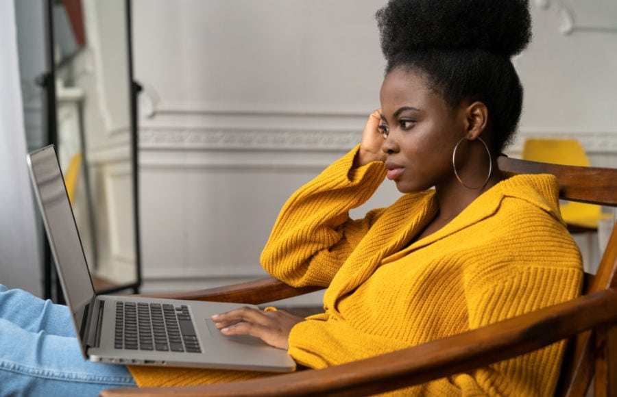 adult woman looking deep in thought while researching how to pay for grad school on laptop