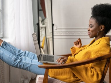 cheerful black woman in yellow using laptop with feet propped up