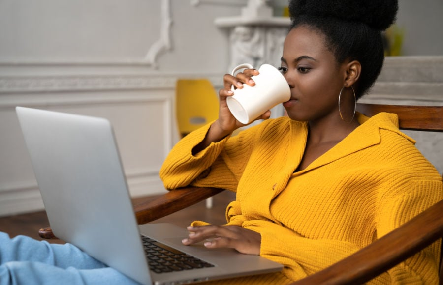 millenial in yellow drinking cup of coffee while using laptop