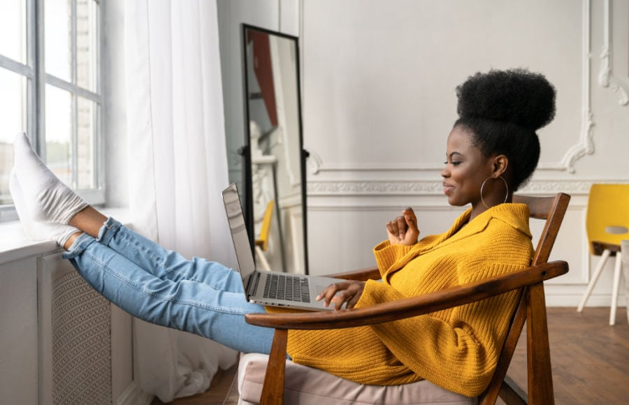 smiling young adult woman reading on laptop while sitting comfortably by a window
