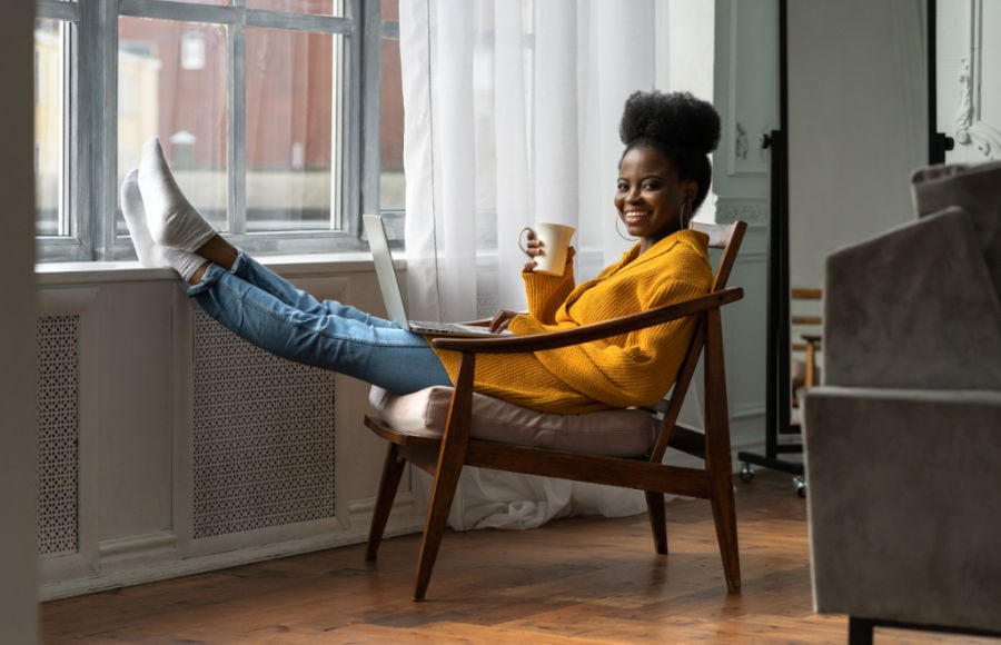 black woman wearing yellow cardigan with feet propped up on window sill while enjoying a cup of coffee