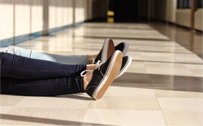 pair of legs crossed sitting on the floor in school hallway