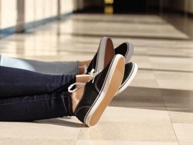 friends wearing matching sneakers in a high school hallway