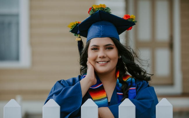 smiling graduate posed leaning against picket fence wearing her blue cap and gown