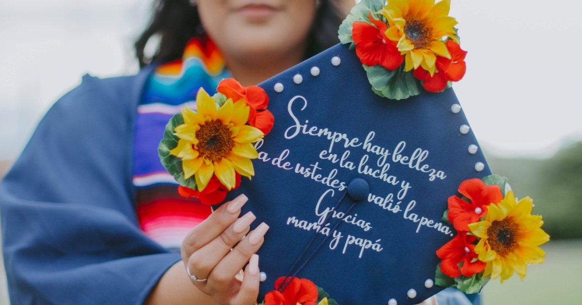 graduation cap decorated with colorful flowers and a spanish quote