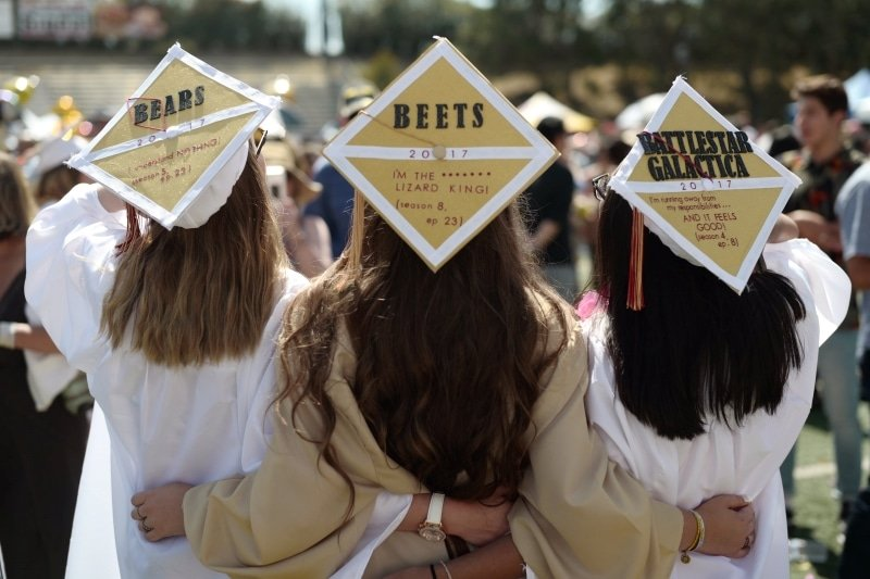 3 graduating girls standing together in gold and white graduation robes with decorated caps