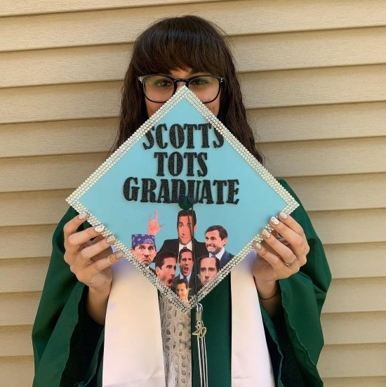 """graduate holding light blue graduation cap that reads """"scotts tots grad"""" referencing the office"""
