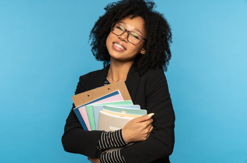 organized student smiling while holding notebooks and papers